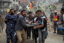 Emergency rescue workers carry a victim on a stretcher after Dharara tower collapsed on April 25, 2015 in Kathmandu, Nepal. Photo by Omar Havana/Getty Images.
