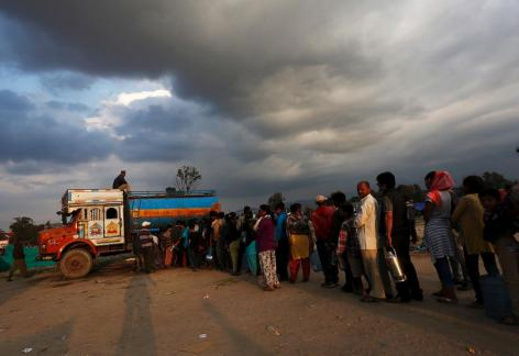 People stand in line to get drinking water.