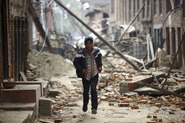 A man runs past damaged houses as aftershocks of an earthquake are felt a day after the earthquake in Bhaktapur, Nepal April 26, 2015. Photo by Navesh Chitrakar/REUTERS
