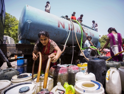 Indian residents fill water containers from a government water supply truck in New Delhi on May 22, 2013. With summer temperatures hovering around 45 degrees, residents are struggling with water shortages as Delhi has been going through a severe water shortage for the past few days after the upper Ganga Canal was shut for repairs. AFP PHOTO/ Andrew Caballero-ReynoldsAndrew Caballero-Reynolds/AFP/Getty Images