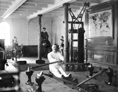 """TW McCawley, """"physical educator"""", on the rowing machine, the man behind is Harland and Wolfe electrician William Parr sitting on a mechanical camel. Both men were lost in the disaster."""