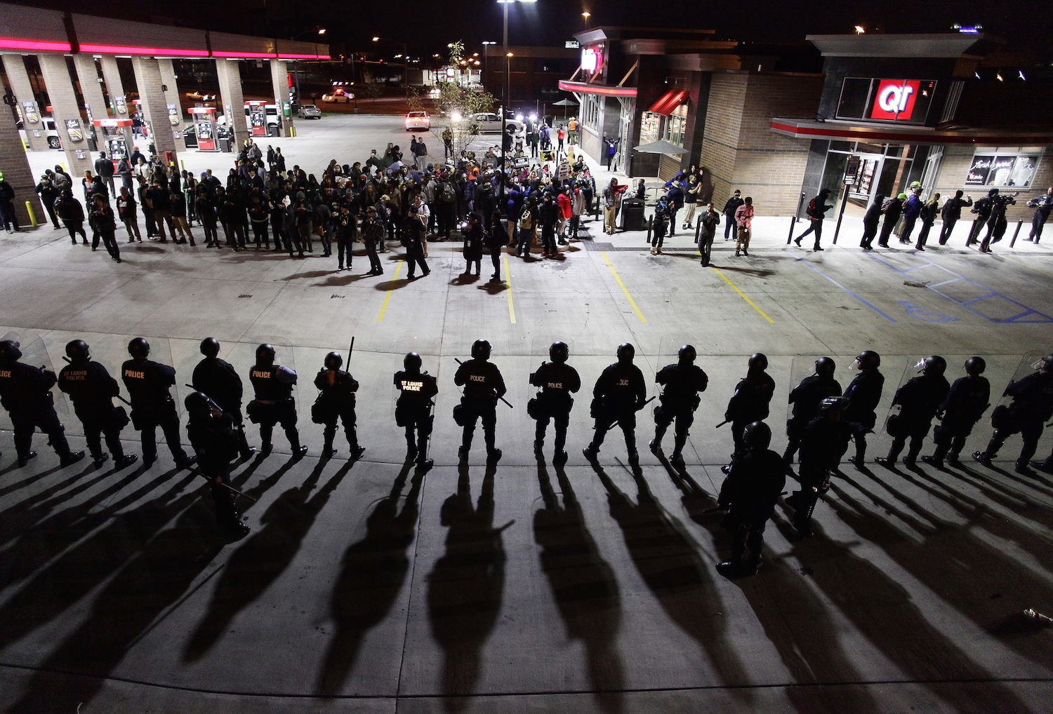 Police officers in riot gear hold a line as they watch demonstrators protest  the shooting death of Michael Brown and 18-year-old Vonderrit Myers Jr. at a QuikTrip convince store and gas station October, 12 2014 in St. Louis, Missouri. Civil rights organizations, protest groups and people from around the country were protesting the August 9 shooting of Brown, which involved Ferguson Police officer Darren Wilson and Meyers, who was shot and killed last week by an off duty St. Louis police officer.    AFP PHOTO/Joshua Lott        (Photo credit should read Joshua LOTT/AFP/Getty Images)